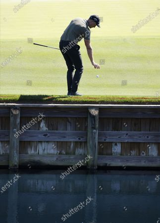 Henrik Stenson of Sweden takes a drop near the water hazard on the twelfth hole during the first round of THE PLAYERS Championship golf tournament at TPC Sawgrass, in Ponte Vedra Beach, Florida, USA, 11 March 2021.