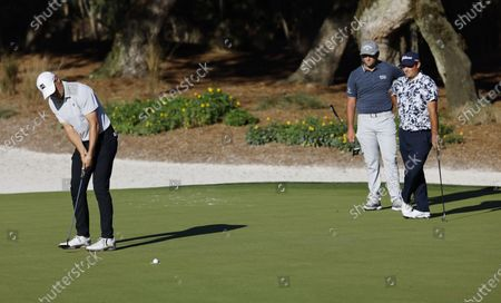 Jordan Spieth of the US (L) putts as Jon Rahm of Spain (C) and Patrick Reed of the uS (R) watch on the fourteenth hole during the first round of THE PLAYERS Championship golf tournament at TPC Sawgrass, in Ponte Vedra Beach, Florida, USA, 11 March 2021.