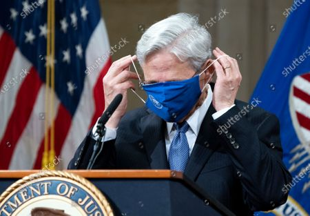President Joe Biden's pick for attorney general Merrick Garland adjusts his face mask after speaking to staff on his first day at the Department of Justice, in Washington. Garland, a one time Supreme Court nominee under President Obama, was confirmed Wednesday by a Senate and will be sworn in later today