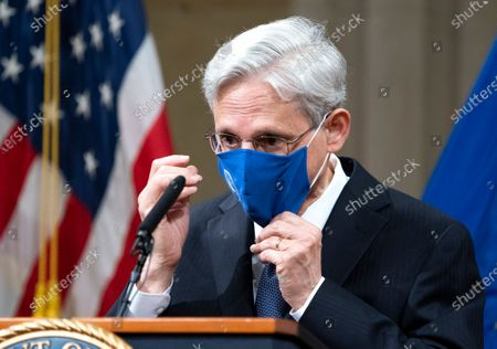 President Joe Biden's pick for attorney general Merrick Garland, adjusts his mask after addressing staff on his first day at the Department of Justice, in Washington. Garland, a one time Supreme Court nominee under President Obama, was confirmed Wednesday by a Senate and will be sworn in later today