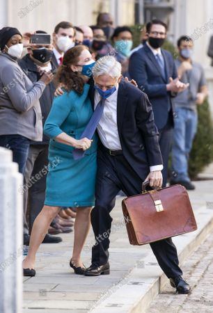 President Joe Biden's pick for attorney general Merrick Garland, hugs his wife Lynn as he arrives for his first day at the Department of Justice, in Washington. Garland, a one time Supreme Court nominee under President Obama, was confirmed Wednesday by a Senate and will be sworn in later today