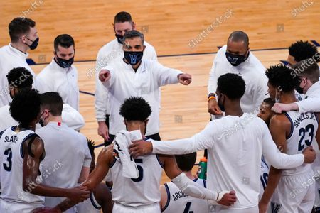 Villanova head coach Jay Wright, center, gives his team instruction during the first half of an NCAA college basketball game against Georgetown in the quarterfinals of the Big East conference tournament, in New York