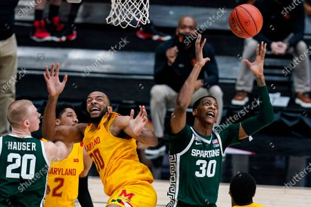 Michigan State forward Marcus Bingham Jr. (30) grabs a rebound over Maryland forward Galin Smith (30) in the first half of an NCAA college basketball game at the Big Ten Conference tournament in Indianapolis