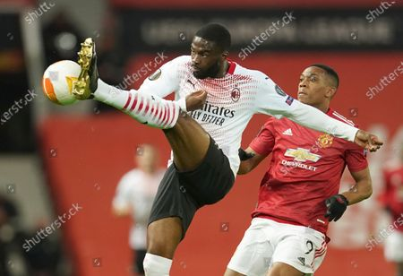 Stock Photo of Milan's Fikayo Tomori, left, and Manchester United's Anthony Martial challenge for the ball during the Europa League round of 16 first leg soccer match between Manchester United and AC Milan at Old Trafford in Manchester, England