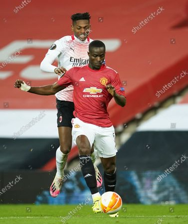 Milan's Rafael Leao, left, and Manchester United's Eric Bailly challenge for the ball during the Europa League round of 16 first leg soccer match between Manchester United and AC Milan at Old Trafford in Manchester, England