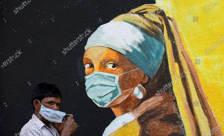 A man wearing a face mask walks past a graffiti of Girl with a Pear Earring by Dutch painter Johannes Vermeer in Mumbai. Despite the spike in coronavirus cases in Maharashtra state, people do not adhere to the guidelines given by the government to follow social distance, wear mask and use sanitizer.