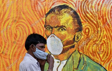 A man wearing a face mask walks past a graffiti of Vincent Van Gogh in Mumbai. Despite the spike in coronavirus cases in Maharashtra state, people do not adhere to the guidelines given by the government to follow social distance, wear mask and use sanitizer.