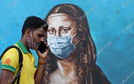 A man talking on a phone walks past a graffiti of Mona Lisa in Mumbai. Despite the spike in coronavirus cases in Maharashtra state, people do not adhere to the guidelines given by the government to follow social distance, wear mask and use sanitizer.