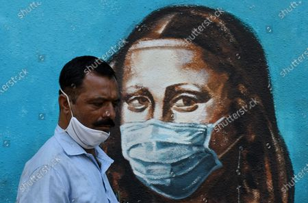 A man wearing a face mask walks past a graffiti of Mona Lisa in Mumbai. Despite the spike in coronavirus cases in Maharashtra state, people do not adhere to the guidelines given by the government to follow social distance, wear mask and use sanitizer.