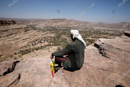 A Yemeni man sits on top of a mountain overlooking the Wadi Dhahr valley where the Dar al-Hajar (Rock Palace) is perched atop a rock pinnacle on the outskirts of Sana'a, Yemen, 10 March 2021 (issued 11 March 2021). The historical five-storey palace of Dar al-Hajar (Rock Palace) was built in 1786 AD and is now one of Yemen's most popular tourist destinations, perching atop a rock pinnacle on the outskirts of Sana'a.