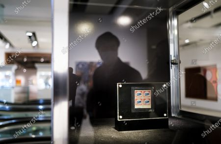 A person looks at the 1918 24-Cent Inverted Jenny Plate Block stamp page seen during a preview of an upcoming auction at Sotheby's in New York, New York, USA, 11 March 2021. The sheet of stamps is expected to sell for an estimated 5 - 7 million dollars / 4.1 - 5.8 million euros during an auction of items belonging to designer Stuart Weitzman on 08 June 2021 in New York.