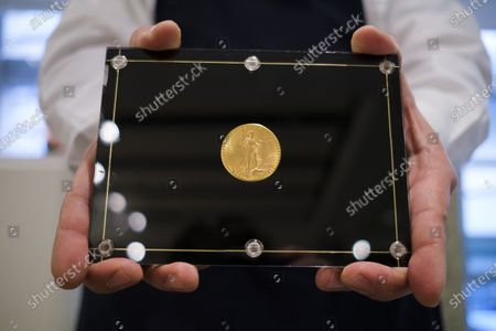 A Sotheby's employee holds the 1933 Double Eagle gold coin during a preview of an upcoming auction at Sotheby's in New York, New York, USA, 11 March 2021. The coin, which is the only one of its kind that can be legal owned privately, is expected to sell for an estimated 10 - 15 million dollars / 8 - 12 million euros during an auction of items belonging to designer Stuart Weitzman on 08 June 2021 in New York.