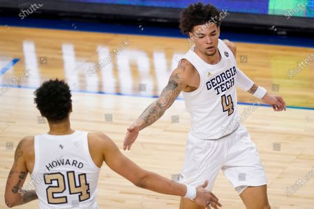 Georgia Tech guard Jordan Usher (4) celebrates a basket with teammate forward Rodney Howard (24) during the second half of an NCAA college basketball game against Miami in the quarterfinal round of the Atlantic Coast Conference tournament in Greensboro, N.C