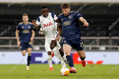 Tottenham's Davinson Sanchez vies for the ball with Dinamo Zagreb's Bruno Petkovic, right, during the Europa League round of 16, first leg, soccer match between Tottenham Hotspur and Dinamo Zagreb at the Tottenham Hotspur Stadium in London, England