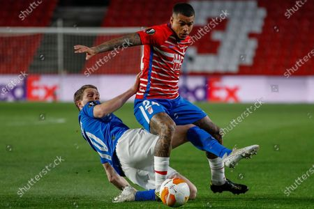 Stock Photo of Granada's Kenedy, right, vies for the ball with Molde's Bjorn Bergmann Sigurdarson during the during the Europa League, round of 16, first leg soccer match between Granada and Molde FK at the Los Carmenes stadium in Granada, Spain