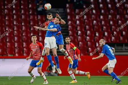 Molde's Bjorn Bergmann Sigurdarson, front, fights for the ball with Granada's Maxime Gonalons during the during the Europa League, round of 16, first leg soccer match between Granada and Molde FK at the Los Carmenes stadium in Granada, Spain