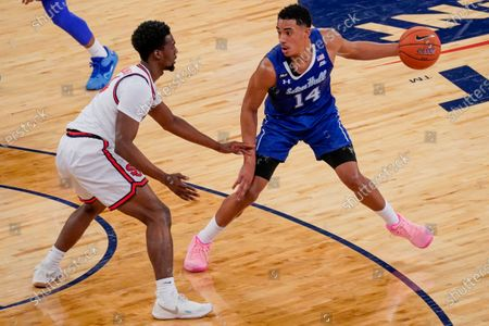 Stock Photo of Seton Hall guard Jared Rhoden (14) drives against St. John's guard Greg Williams Jr. (4) during the first half of an NCAA college basketball game in the quarterfinals of the Big East conference tournament, in New York