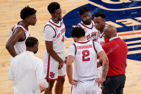 St. John's head coach Mike Anderson, right, gives his team instruction during the second half of an NCAA college basketball game against Seton Hall in the quarterfinals of the Big East conference tournament, in New York