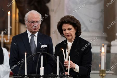 King Carl Gustaf and Queen Silvia light candles during a Memorial service at Drottningholm Palace Church March 11, 2021. Due to the anniversary of the first reported covid-19-related death in Sweden, a service was held on Thursday in Drottningholm's castle church., The service was initiated by His Majesty, who in this way wanted to honor the memory of the victims of the pandemic.,