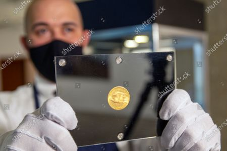 Sotheby's art handler Dustin Marino holds up a 1933 Double Eagle gold coin in New York on . The auction house projects the coin from the collection of fashion designer Stuart Weitzman will sell for 10 to 15 million dollars when auctioned in June