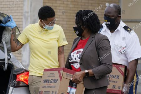 Provine High School physics teacher Raven Thompson, left, adjusts the trunk while principal Shelita Brown and JROTC Army Instructor Major Daniel McGee, carry cases of water to the vehicle of a Jackson, Miss., resident, . The Jackson Public School District set up sites at several schools to help residents who still are under a boil water notice. Over 400 meals were given out as well as the cases of water that school officials hope will be used for cooking since although water pressure has generally returned to much of the city, the water has yet to pass water quality tests