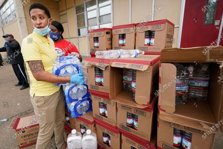 Provine High School physics teacher Raven Thompson, grabs a case of bottled drinking water to be placed in a vehicle of a Jackson, Miss., resident, . The Jackson Public School District set up sites at several schools to help residents who still are under a boil water notice. Over 400 meals were given out as well as the cases of water that school officials hope will be used for cooking since although water pressure has generally returned to much of the city, the water has yet to pass water quality tests