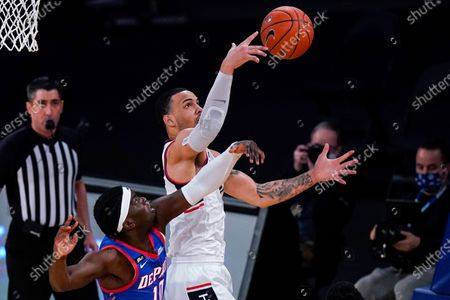 Stock Image of Connecticut's Tyrese Martin, right, fights for control of the ball with DePaul's Ray Salnave during the first half of an NCAA college basketball game in the Big East mens' tournament, in New York