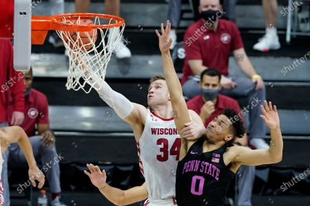 Wisconsin's Brad Davison (34) is fouled by Penn State's Myreon Jones (0) as he goes up for a shot during the second half of an NCAA college basketball game at the Big Ten Conference tournament, in Indianapolis