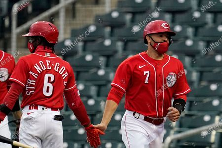 Cincinnati Reds' Eugenio Suarez (7) celebrates his run scored against the Chicago White Sox with Reds' Dee Strange-Gordon (6) during the first inning of a spring training baseball game, in Goodyear, Ariz