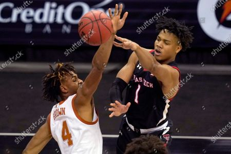 Texas Tech guard Terrence Shannon Jr. (1) passes while covered by Texas forward Greg Brown (4) during the second half of an NCAA college basketball game in the quarterfinal round of the Big 12 men's tournament in Kansas City, Mo