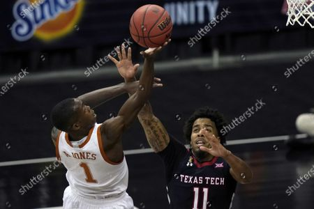 Texas guard Andrew Jones (1) shoots over Texas Tech guard Kyler Edwards (11) during the second half of an NCAA college basketball game in the quarterfinal round of the Big 12 men's tournament in Kansas City, Mo., . Texas defeated Texas Tech 67-66