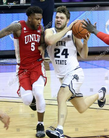 Stock Photo of Utah State guard Rollie Worster (24) drives as UNLV guard David Jenkins Jr. (5) defends during the second half of an NCAA college basketball game in the quarterfinals of the Mountain West Conference men's tournament, in Las Vegas