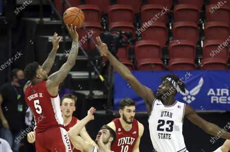 Stock Picture of Guard David Jenkins Jr. (5) shoots as Utah State center Neemias Queta (23) defends during the second half of an NCAA college basketball game in the quarterfinals of the Mountain West Conference men's tournament, in Las Vegas