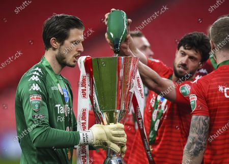 Jason Lowe of Salford City fills the trophy with champagne for Václav Hladký of Salford City