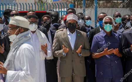 Somalia's President Mohamed Abdullahi Mohamed, center, and other officials pray over the body of former president Ali Mahdi Mohamed, who died of COVID-19 earlier this week in neighboring Kenya, at a state funeral held at the airport in Mogadishu, Somalia . Somalia has declared three days of mourning during which the national flag will be lowered to half-staff in honor of the former president, who was 86