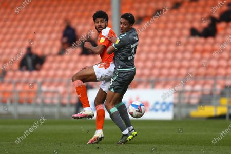 Blackpool's Ellis Simms and James Hill of Fleetwood