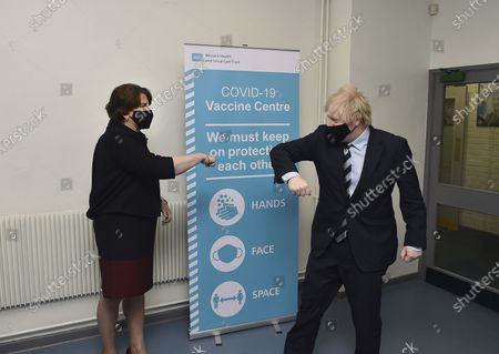 Britain's Prime Minister Boris Johnson is greeted with an elbow bump by First Minister Arlene Foster during a visit to the Lakeland Forum vaccination centre in Enniskillen, Northern Ireland