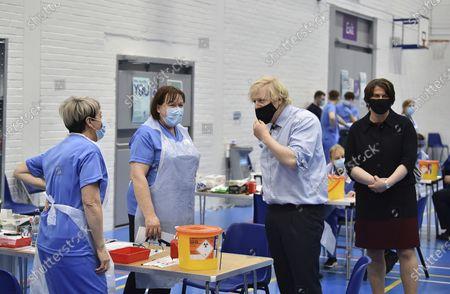 Britain's Prime Minister Boris Johnson and First Minister Arlene Foster, right, visit the Lakeland Forum vaccination centre in Enniskillen, Northern Ireland