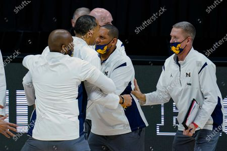 Michigan head coach Juwan Howard, second from left foreground, is restrained after being ejected from the game in the second half of an NCAA college basketball game against Maryland at the Big Ten Conference tournament in Indianapolis