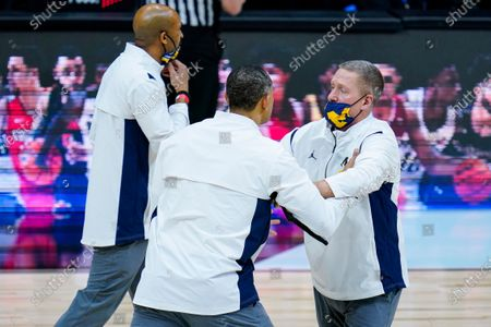 Michigan head coach Juwan Howard, center, is restrained after being ejected from the game in the second half of an NCAA college basketball game against Maryland at the Big Ten Conference tournament in Indianapolis