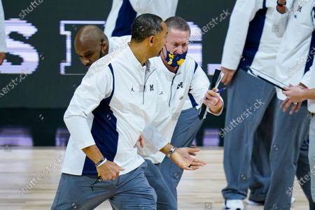 Michigan head coach Juwan Howard, front, is restrained after being ejected from the game in the second half of an NCAA college basketball game against Maryland at the Big Ten Conference tournament in Indianapolis