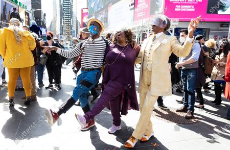 Broadway actors Sahr Ngaujah (L), Lilias White (C) and Andre De Shields (R) spontaneous sing and dance together following a pop-up performance in Times Square called 'We Will Be Back' which was organized by the theater community to commemorate a year since theaters on Broadway were shut down due to the coronavirus pandemic in New York, New York, USA, 12 March 2021. Broadway shows, and other live entertainment venues, are hoping to reopen later in the year but there are still questions about the financial viability of many shows if seating capacity continues to be limited by worried over the spread of COVID-19.
