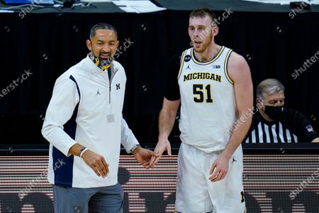 Michigan head coach Juwan Howard talks with Austin Davis as they played Maryland in the first half of an NCAA college basketball game at the Big Ten Conference tournament in Indianapolis