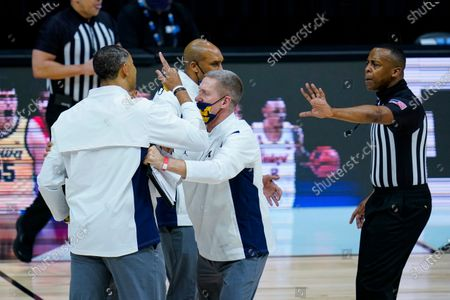 Michigan head coach Juwan Howard is restrained after being ejected from the game in the second half of an NCAA college basketball game against Maryland at the Big Ten Conference tournament in Indianapolis