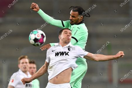 Augsburg's Raphael Framberger in action against Moenchengladbach's Valentino Lazaro (up) during the German Bundesliga soccer match between FC Augsburg and Borussia Moenchengladbach in Augsburg, Germany, 12 March 2021.