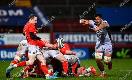 Nick McCarthy of Munster performs a box kick under pressure from Sam Lousi of Scarlets