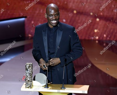 """French actor Jean-Pascal Zadi poses with his trophy after receiving the Best Male Newcomer award for the movie """"Tout simplement noir"""" (Simply Black)"""
