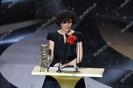 """Stock Image of French film producer Catherine Bozorgan delivers a speech on behalf of French actor and film director Albert Dupontel after receiving the Best Feature Film award for the movie """"Adieu les cons"""" (Bye Bye Morons) at 46th Cesar Film Awards 2021 ceremony at l'Olympia in Paris on March 12, 2021 in Paris, France."""