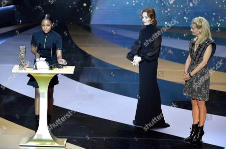 """Stock Picture of French actress Fathia Youssouf receives the Best Female Newcomer award for the movie """"Mignonnes"""" (Cuties) from French actress Isabelle Huppert and French actress and Master of Ceremony Marina Fois"""