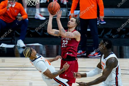 Illinois guard Adam Miller, left, draws the charge from Rutgers guard Caleb McConnell (22) during the first half of an NCAA college basketball game at the Big Ten Conference men's tournament in Indianapolis